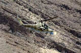 COMBINED SECURITY TRANSITION COMMAND - AFGHANISTAN, KABUL - An Mi-35 attack helicopter fires during a gunnery training mission May 27 over the East River Range Complex near Bagram Airbase. This mission was the first time 57 mm rockets and the 12.7 mm cannon have been fired by the Afghan National Army Air Corps in more than eight years, and will eventually allow the Afghans to provide their own close air support. (Combat Camera photo courtesy of Combined Airpower Transition Force)