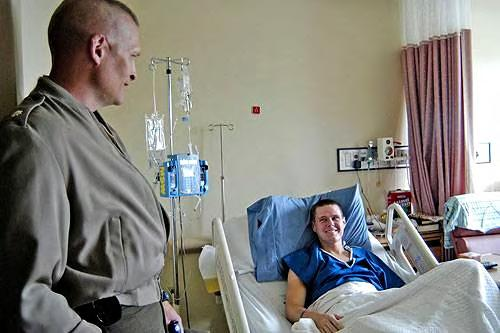 Lt. Col. Maxwell (standing at left) stops by to visit with LCpl. Brian Erickson (in bed at right) at the Naval Hospital at Camp Lejeune. July 2005